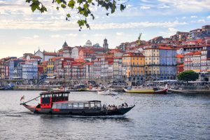 Porto, Portugal old town ribeira aerial promenade view with colorful houses, traditional facades, old multi-colored houses with red roof tiles, Douro river and boats. Aerial cityscape image of Porto